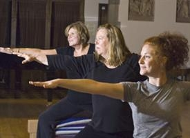 three women doing yoga with arms outstretched