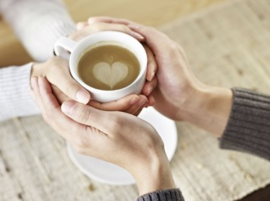 Two people's hands wrapped around a cup of coffee with a heart shape inside
