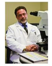 Dr. David G. Hicks wearing a white lab coat and tie sitting in front of a microscope.