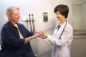 Doctor examining an elderly woman's joints