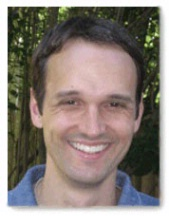 A headshot of Dr. Joshua C. Munger in front of trees.