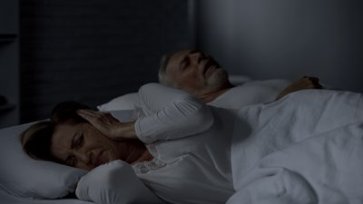 woman plugging her ears while man is snoring
