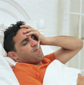 man sick in bed with thermometer in his mouth