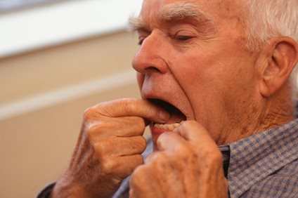 senior man flossing his teeth