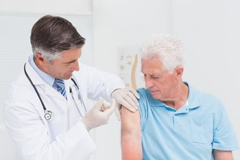 doctor giving vaccine to older gentleman