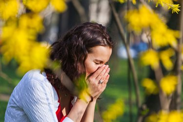 woman in field sneezing with hayfever