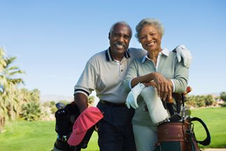 senior couple smiling on golf course
