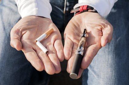 hands holding cigarette and e-cigarette