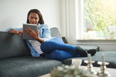 woman sitting on a sofa using an ipad