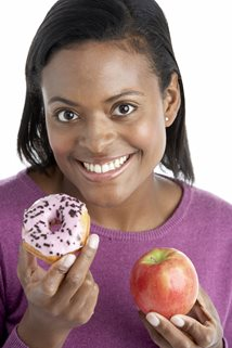 young woman choosing between an apple and a banana