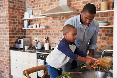 young father washing vegetables at the kitchen sink with his son