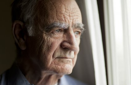 elder abuse victim looking sadly out a window