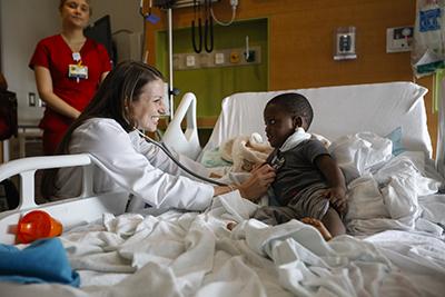 Senior pediatric resident Sarah Hodges, MD, examines Jaired Burnett, 2