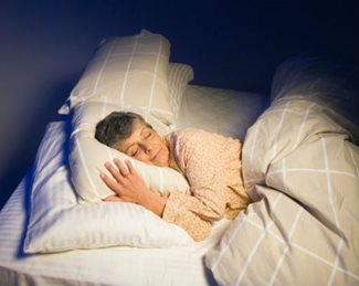 woman sleeping in darkened bedroom
