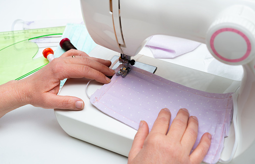 an up-close picture of a person's hands sewing a pastel purple cloth face mask.