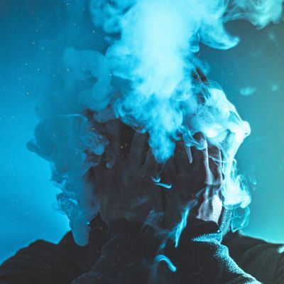 Man with cloud of smoke on his face and blue background, Vaping