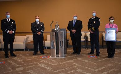 Five firefighters in uniform stand next to a nurse from Wilmot, near the bell they donated to the WCI Greece location.