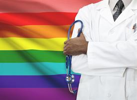 Physician standing in front of a pride flag