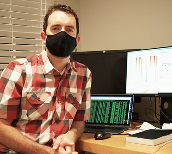 Patrick Murphy, Ph.D., wears a mask and sits next to a computer showing his research results.