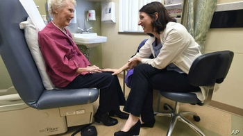 doctors speaks with elderly cancer patient