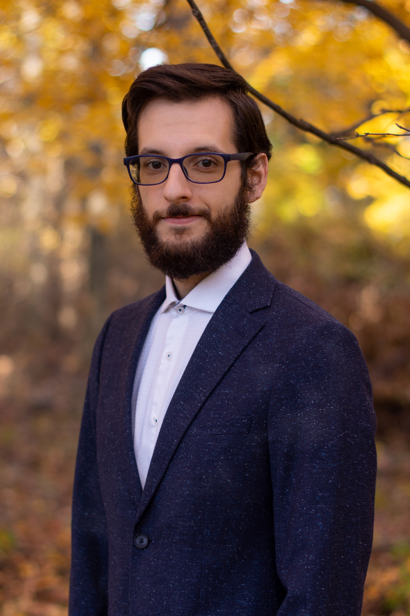 Benjamin is wearing a dark blue blazer over a white button up shirt. He has a full beard dark brown hair and glasses. He is standing outside in front of a golden fall scene.