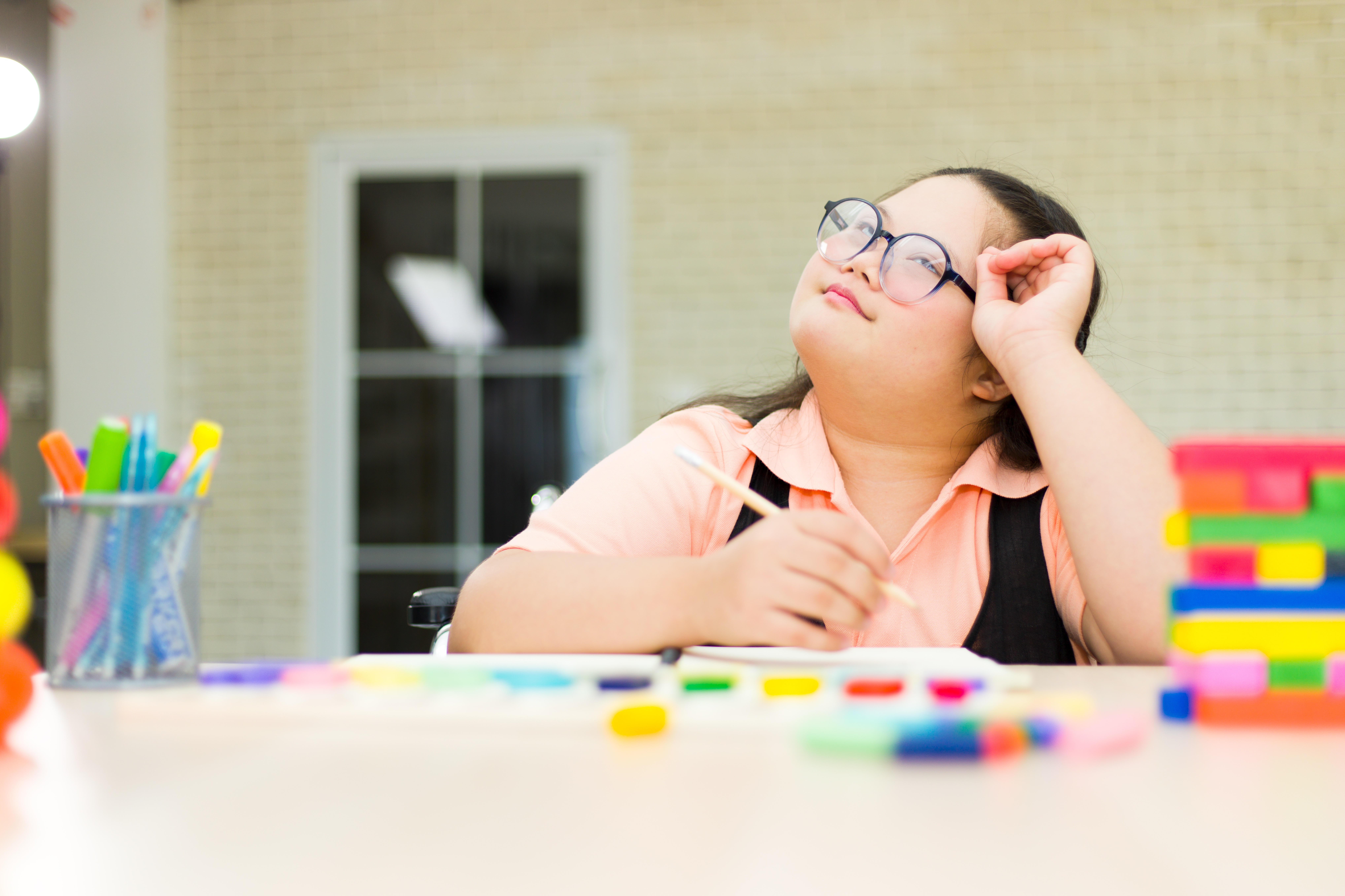 Young girl with an IDD sitting at table with pencil in hand looking up to her right. There are colorful blocks and  markers on the table as well. She is wearing a peach shirt with a black vest and glasses.