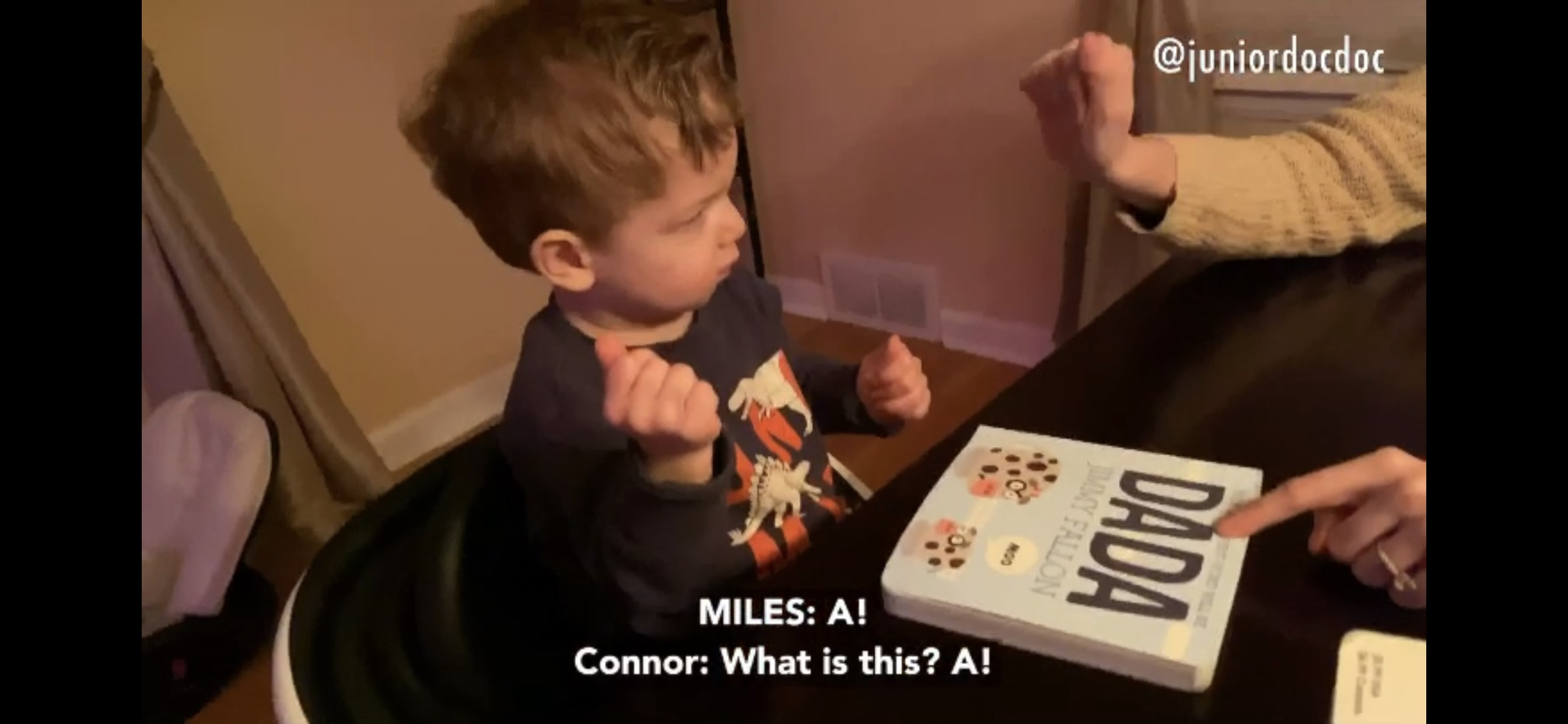 This still image from a video shows Miles fingerspelling the word he is reading on the cover of the book DADA by Jimmy Fallon to his dad, Ian, and mom, Connor.