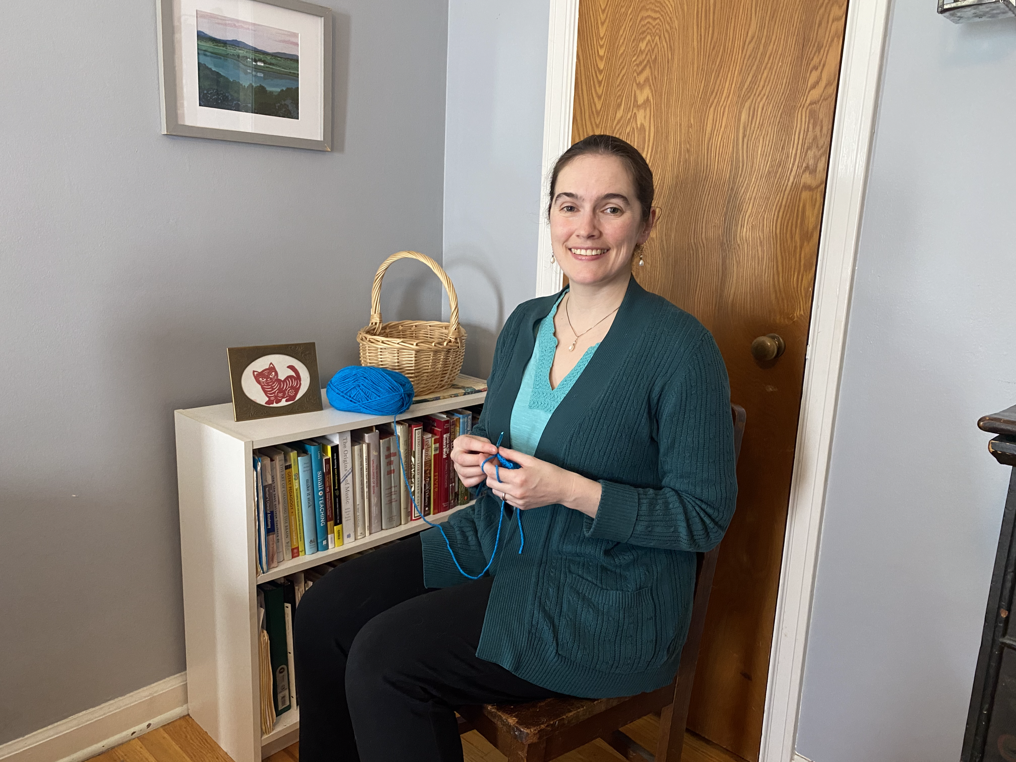 Sarah McConnell, Ph.D. is sitting next to a bookcase knitting. She is wearing a blue shirt and sweater and is smiling with her dark hair pulled back.