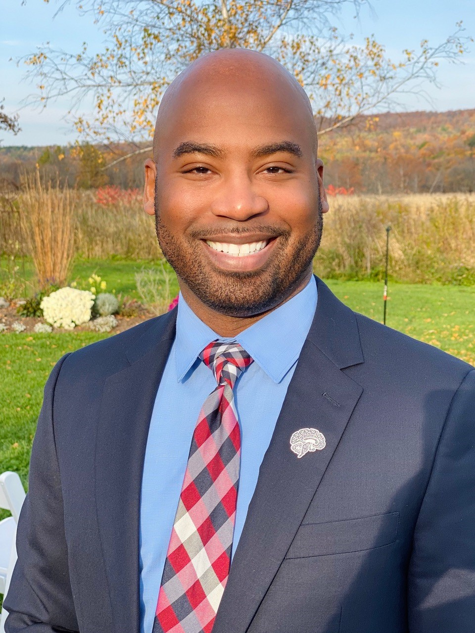 Nathan A. Smith is wearing a dark blue blazer with a blue shirt and red and blue checkered tie. He is smiling witha short beard. He is standing outside on a fall day.