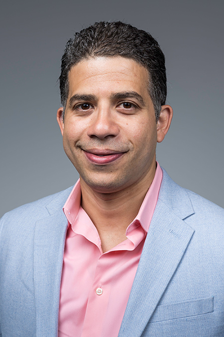 Manuel Gomez-Ramirez is in front of a grey background. He has short dark hair with a slight smile. He is wearing a light pink dress shirt under a light grey suit coat.
