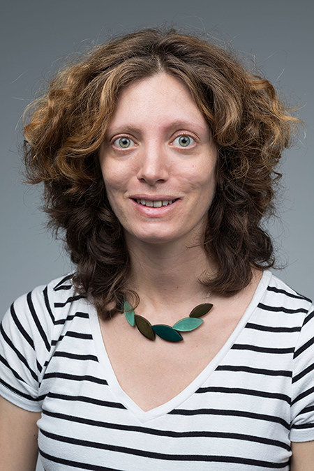 Headshot of Martina Poletti she has curly shoulder length brown hair. She is smiling and wearing a green and black necklace with a white shirt with black strips. She is in front of a grey background.