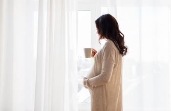 Pregnant woman standing at window holding mug.