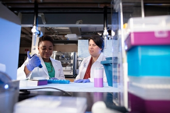 Two female scientists, Nikesha Gilmore and Michelle Janelsins, in a research laboratory