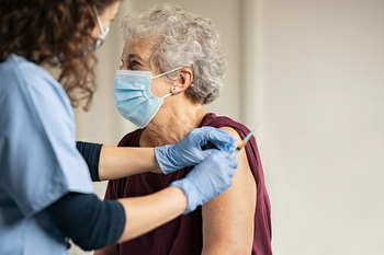 Doctor giving Johnson and Johnson vaccine to senior woman at a rural clinic.