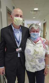 Dr Aram Hezel (masked) stands with his arm around his patient, Dolores House, (masked) at the Wilmot Cancer Institute
