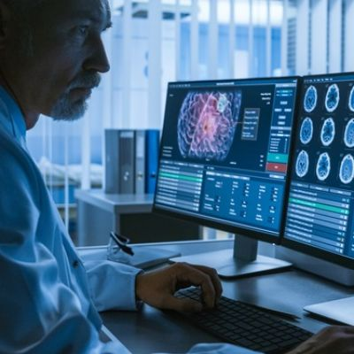 Over the Shoulder Shot of Senior Medical Scientist Working with CT Brain Scan Images on a Personal Computer in Laboratory. Neurologists in Research Center Work on Brain Tumor Cure.