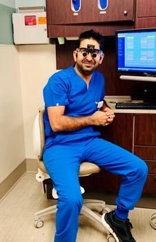 Dr. Kakkar wearing scrubs, seated