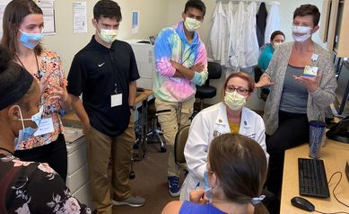 Five students stand around a nurse practitioner and interpreters having a conversation.