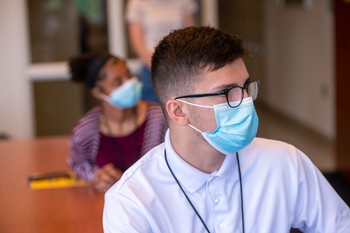 Young adult male wearing a mask listens intently to lecture, while a young woman sits behind him also listening.