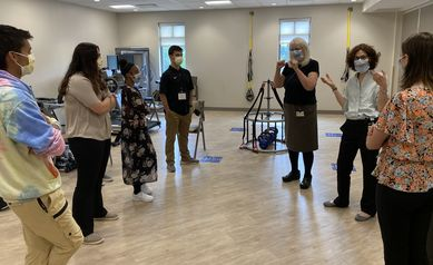 Five students, an interpreter and a physician stand talking in a room with exercise equipment.