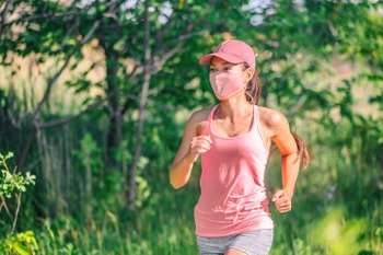 Masked woman jogging in summer park wearing a pink tank top.