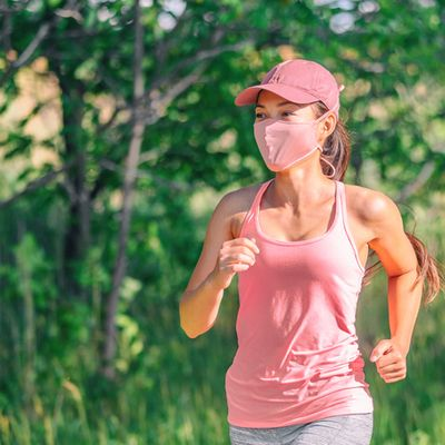 Mask wearing during exersice for COVID-19 protection Asian girl running outside with face covering while exercising jogging on run sport workout in summer park nature. Pink mask, cap, tank top