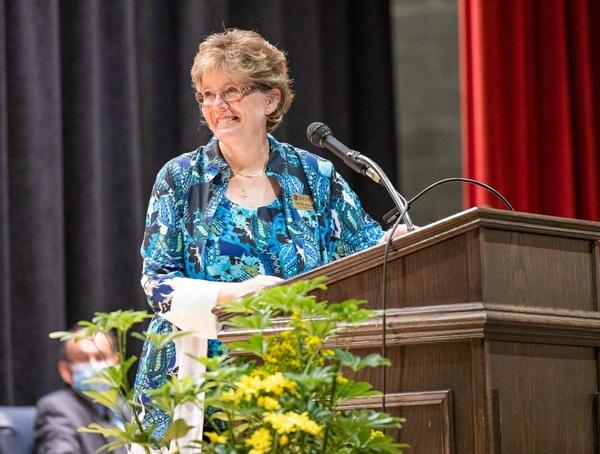 School of Nursing dean Kathy Rideout smiling on stage at pinning