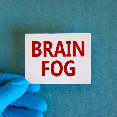 Medical, COVID-19 Pandemic Coronavirus brain fog symbol. Doctor hand holds White card with words 'brain fog'. Metallic pen. Beautiful white background. Copy space. Medical, covid-19 brain fog concept.