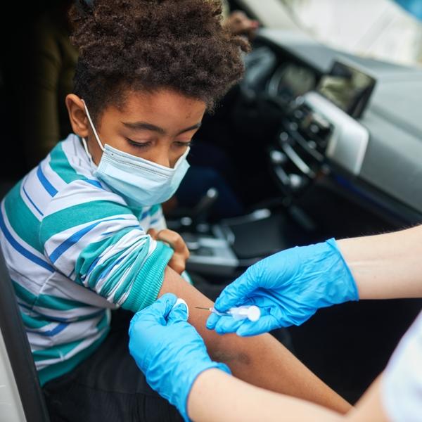 child receives flu shot or COVID vaccine diversity Black