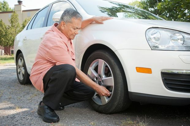 Man uses tire pressure gauge