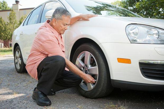 Man uses tire pressure gauge