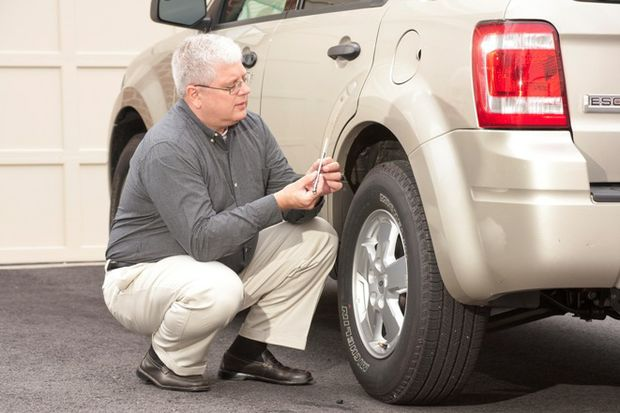 Senior driver looking at tire pressure gauge