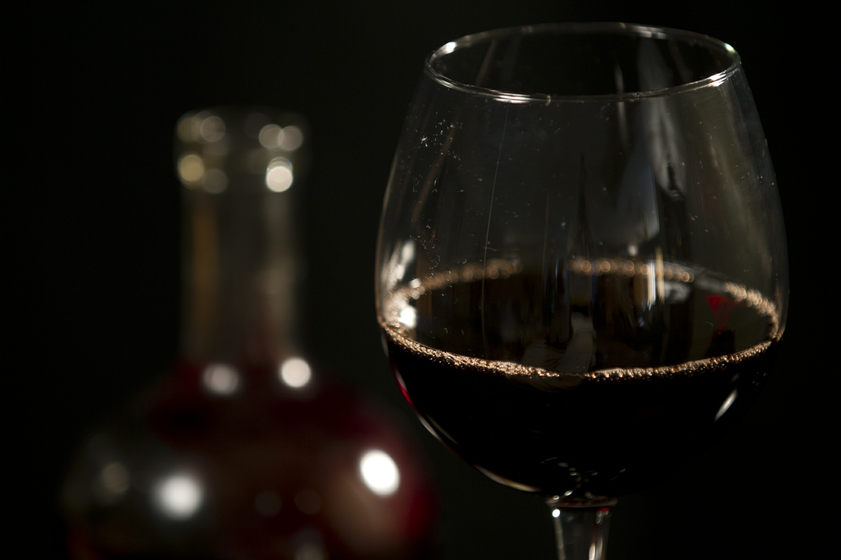 Wine - Red in Glass with bottle close up on glass