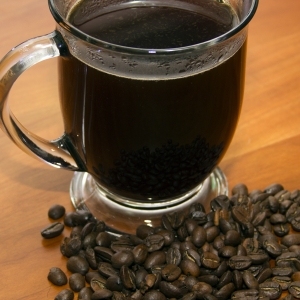 Coffee in Cup with whole beans above Close